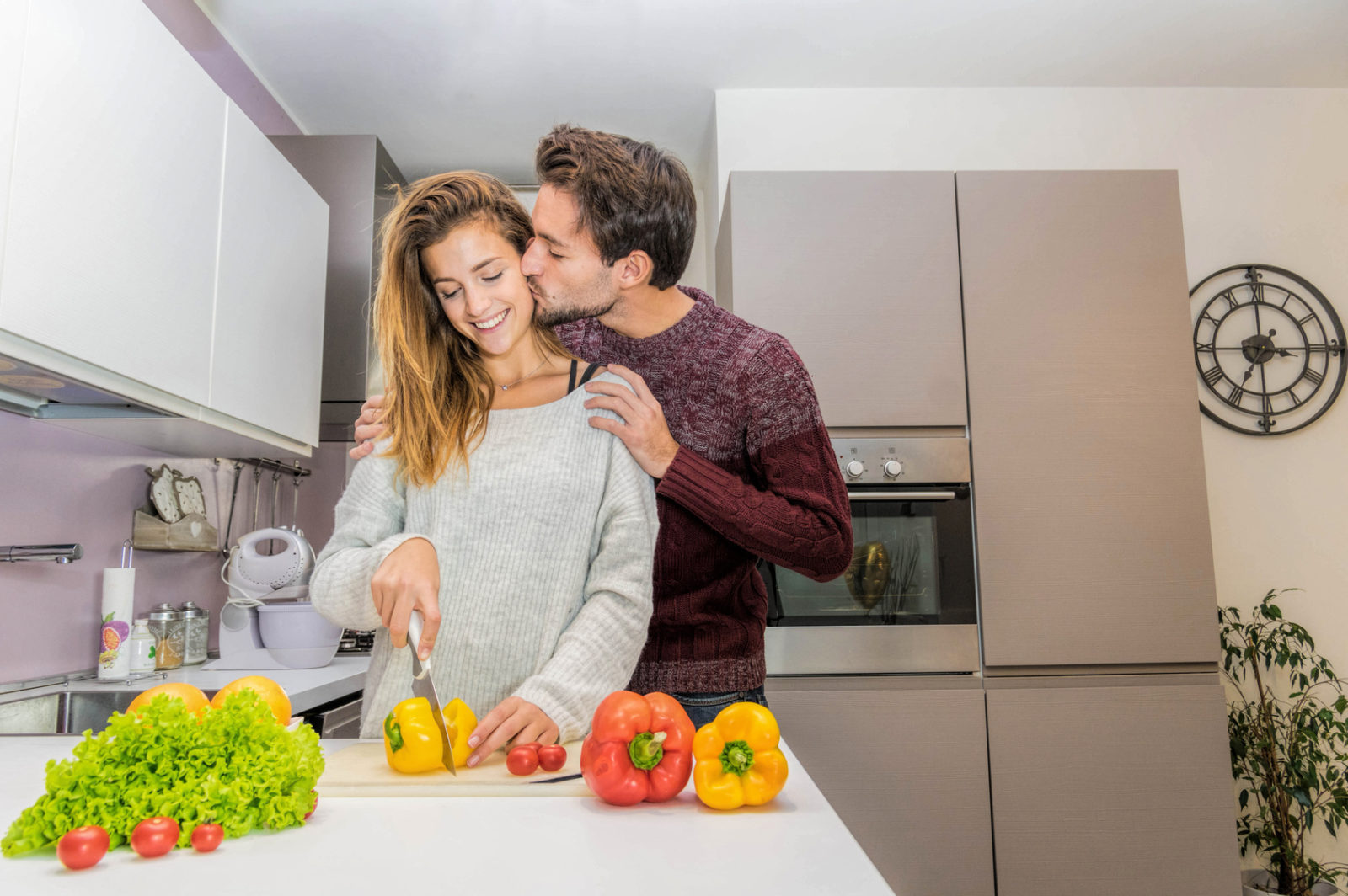 Happy beatiful young couple have fun in modern kitchen indoor while preparing fresh vegetables food salad